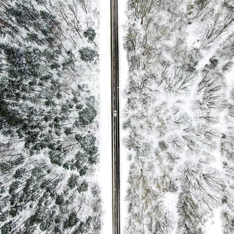 Straße durch den verschneiten Wald - Luftbildaufnahmen im Großformat